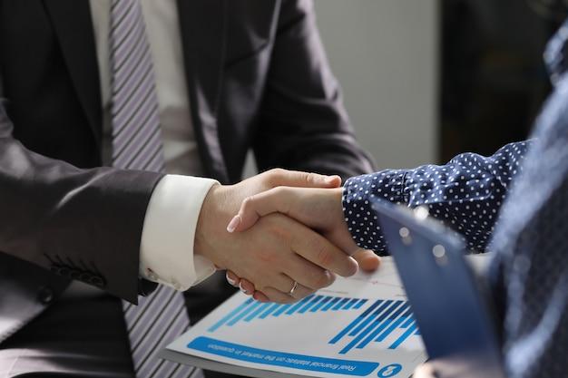 Geschäftsmann- und frauenhand rütteln innenbüro