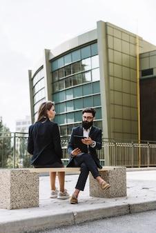 Geschäftsmann und geschäftsfrau, die auf bank vor bürogebäude sitzen