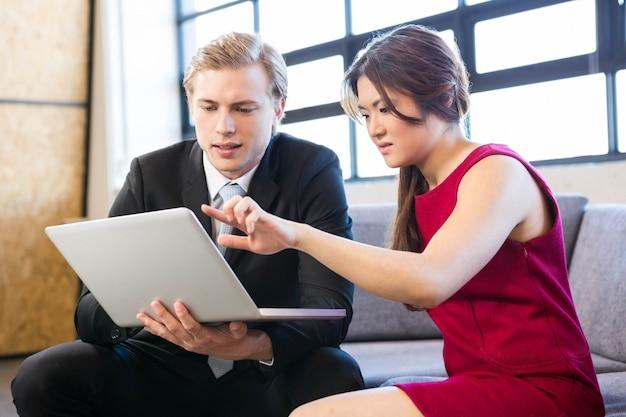 Geschäftsmann und geschäftsfrau, die auf sofa sitzen und laptop im büro betrachten