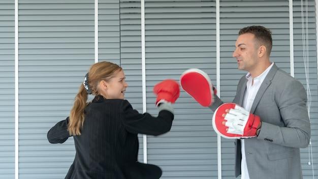Geschäftsmann und geschäftsfrau, die boxhandschuhe tragen. im konzeptgeschäft herausforderung