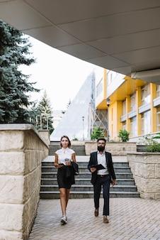 Geschäftsmann und geschäftsfrau, die das mobiltelefon und digitale tablette außerhalb des büros zusammen gehen hält