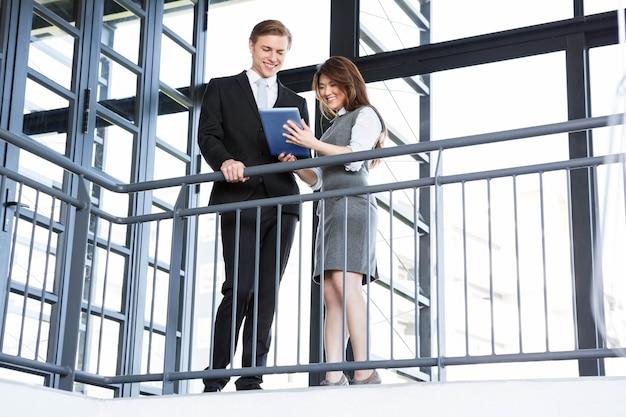 Geschäftsmann und geschäftsfrau, die digitale tablette im büro verwendet