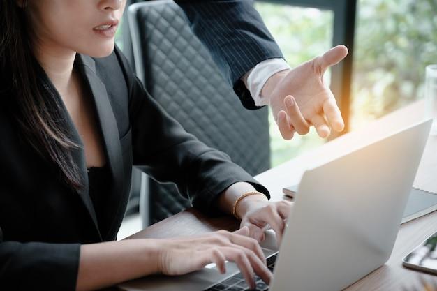 Geschäftsmann und geschäftsfrau, die über vermarktungsplan am konferenzzimmer sich besprechen oder darstellen.