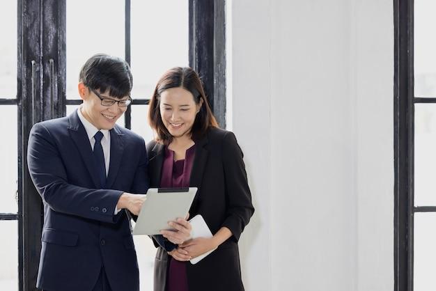 Geschäftsmann und geschäftsfrau, die zusammen einen laptop benutzen, während sie im büro in der nähe eines fensters stehen