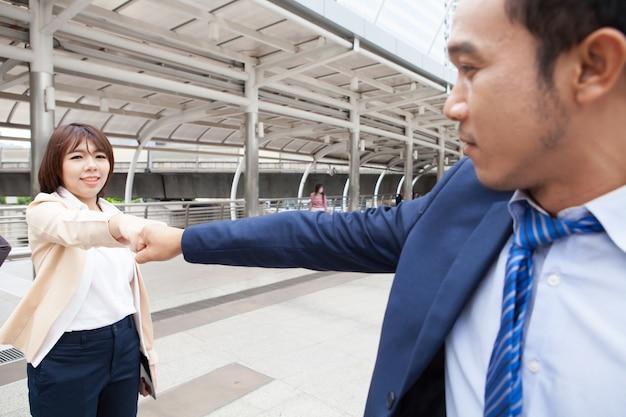 Geschäftsmann und geschäftsfrau faust bump. geschäftsleute tragen anzug eine faustpumpe