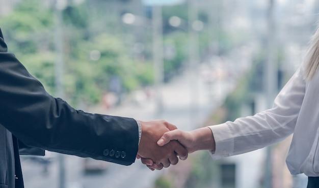 Geschäftsmann und geschäftsfrau geben hand für den erfolg des vertragskonzepts