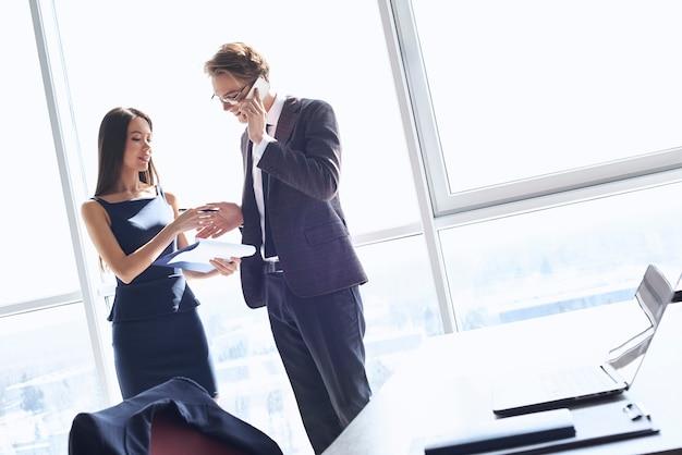Geschäftsmann und geschäftsfrau im büro arbeiten zusammen in der nähe eines fenstermanns, der auf dem smartphone spricht und freudig lächelt, während die frau ihm einen deal gibt