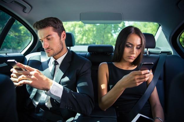 Geschäftsmann und geschäftsfrau mit smartphone auf dem rücksitz im auto