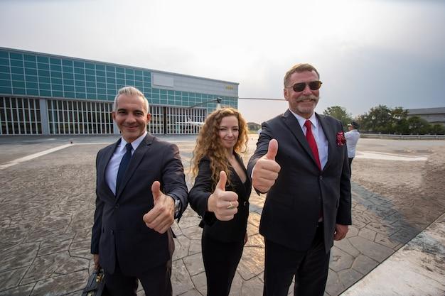 Geschäftsmann und geschäftsfrau tragen schwarzen anzug gehen zusammen mit gepäck auf der öffentlichen straße, geschäftsreisekonzept