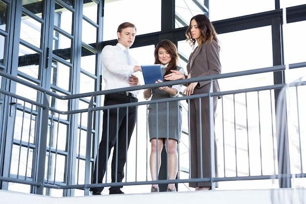 Geschäftsmann und geschäftsfrauen, die digitale tablette im büro betrachten