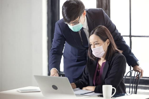 Geschäftsmann und schöne geschäftsfrau sitzen am schreibtisch im coworking office mit gesichtsmaske wegen covid-19