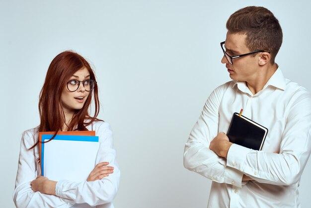 Geschäftsmann und sekretärin halten dokumente kollegen auf einem hellen hintergrund beschnittene ansicht
