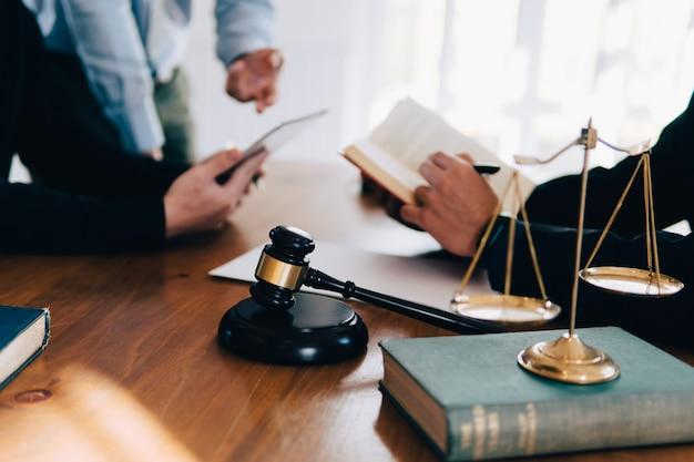 Geschäftsmann und team und rechtsanwälte, die vertragspapiere mit messingskala auf hölzernem schreibtisch im büro besprechen