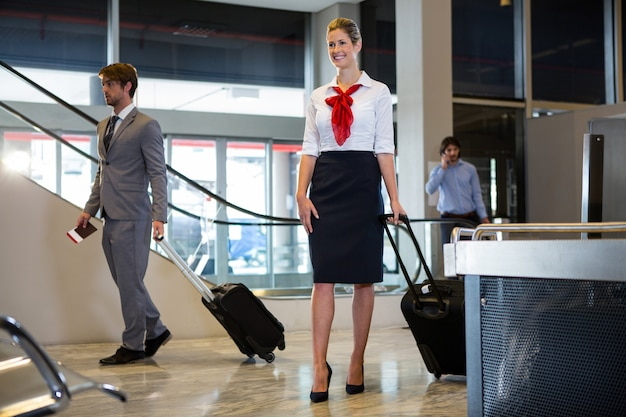 Geschäftsmann und weibliches personal, das mit gepäck im wartebereich geht