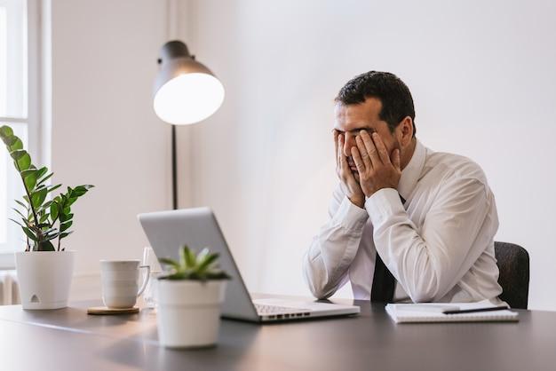 Geschäftsmann unter stress, müdigkeit und kopfschmerzen im büro
