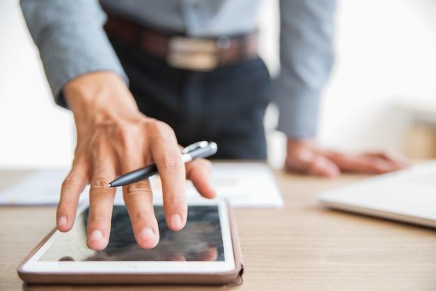 Geschäftsmann unter verwendung der digitalen tablette im büro