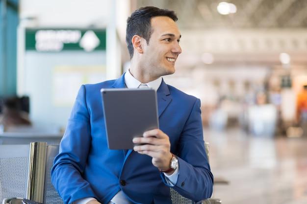 Geschäftsmann unter verwendung der elektronischen tablette in einem flughafen