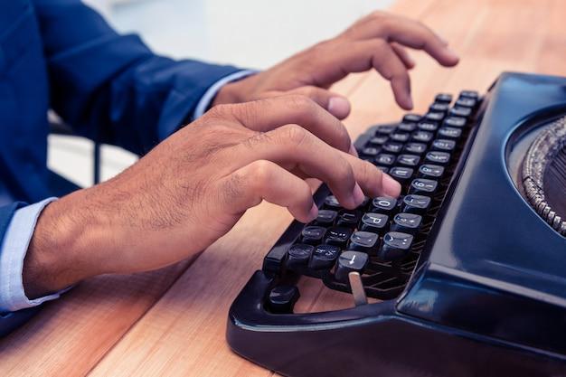 Geschäftsmann unter verwendung der schreibmaschine am hölzernen schreibtisch im büro