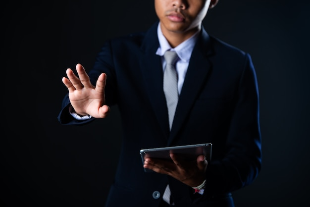 Geschäftsmann unter verwendung der tablette, die verkaufsdaten und wirtschaftswachstumsdiagrammdiagramm, technologie analysiert