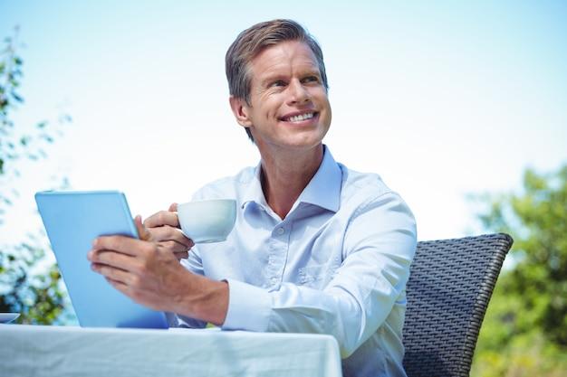 Geschäftsmann unter verwendung der tablette mit kaffee