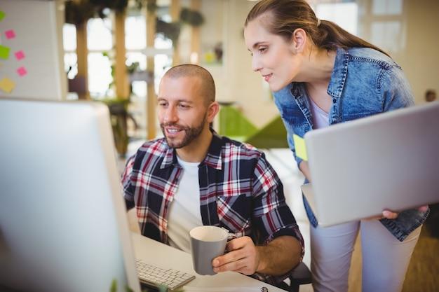 Geschäftsmann unter verwendung des computers beim arbeiten mit weiblichem kollegen