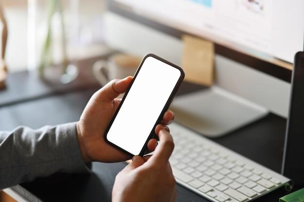 Geschäftsmann unter verwendung des handys auf schreibtisch, intelligentes telefon, das leeren bildschirm für montage zeigt.