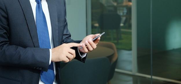 Geschäftsmann unter verwendung des intelligenten telefons innerhalb des bürohaushintergrundes