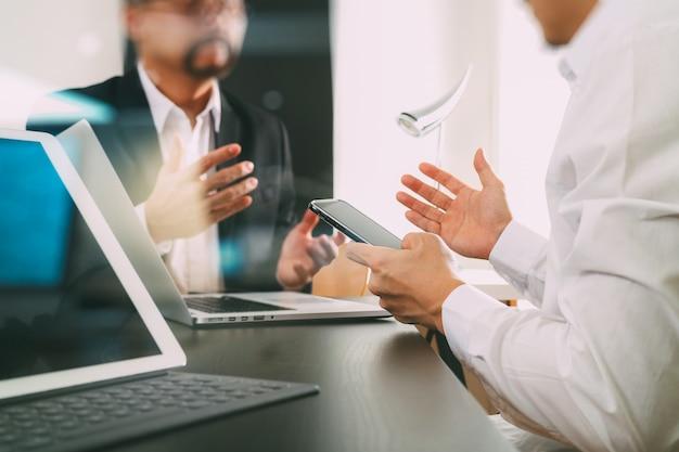 Geschäftsmann unter verwendung des intelligenten telefons und der digitalen tablette und der laptop-computer im modernen büro