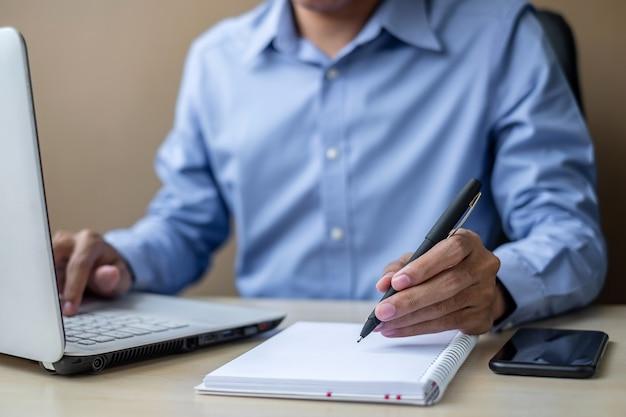 Geschäftsmann unter verwendung des laptopanalyse-marketingplans