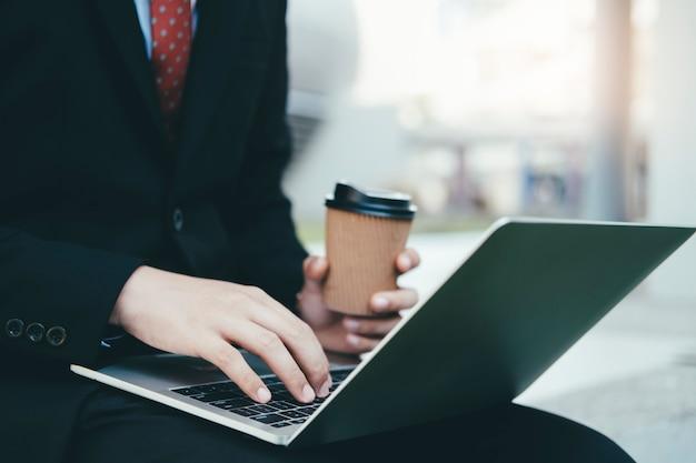 Geschäftsmann unter verwendung des laptops beim sitzen des büros im freien.