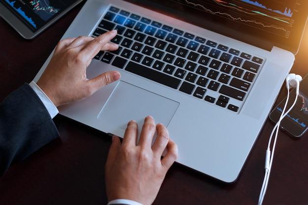 Geschäftsmann unter verwendung des laptops, der mit börsendiagramm auf schirm, geschäft und techn arbeitet