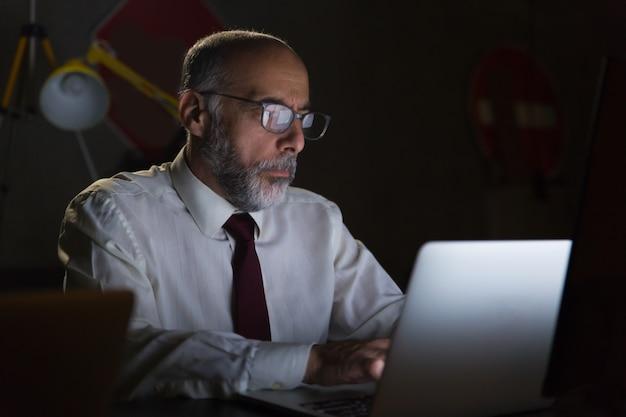 Geschäftsmann unter verwendung des laptops im dunklen büro