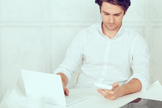 Geschäftsmann unter verwendung des laptops mit tablette und stift