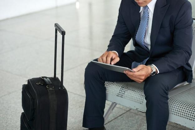 Geschäftsmann unter verwendung des tablet-computers im flughafen