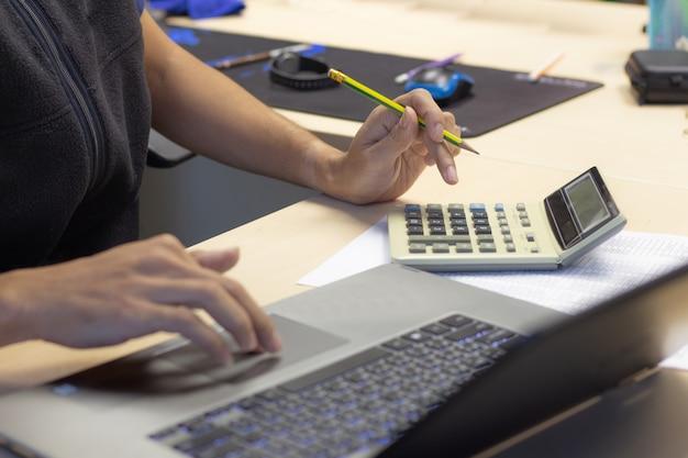 Geschäftsmann unter verwendung des taschenrechners und des computerlaptops für die berechnung des finanzbuchhaltungsbetruges