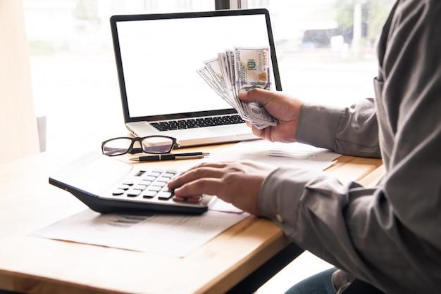 Geschäftsmann unter verwendung des taschenrechners und halten des geldes
