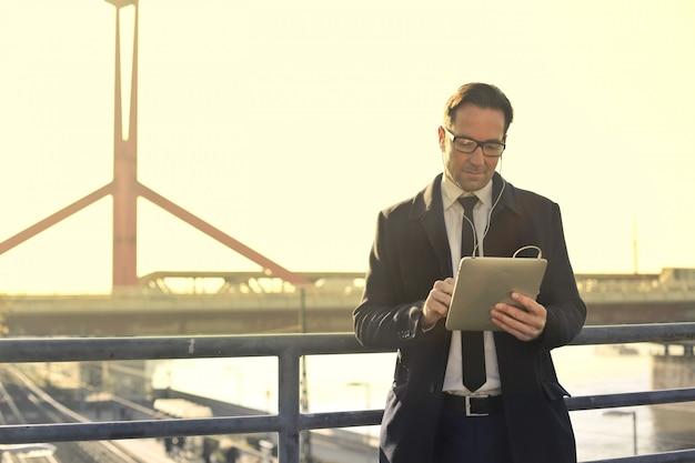 Geschäftsmann unter verwendung einer tablette in der stadt