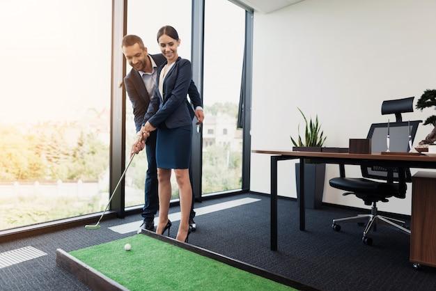 Geschäftsmann unterrichtet seine sekretärin, minigolf zu spielen.