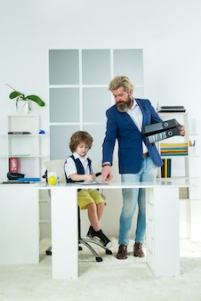 Geschäftsmann vater mit seinem sohn zeichnung auf geschäftspapieren im büro. teamwork und geschäftsfamilienteam. zukünftige bildung, beruf.
