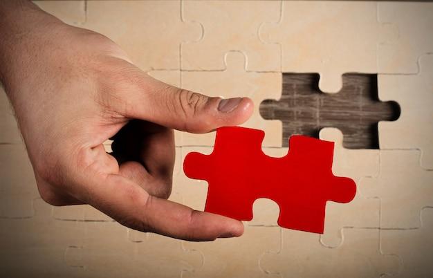 Geschäftsmann vervollständigen ein puzzle, das ein fehlendes stück einfügt