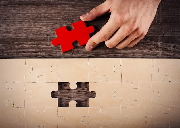 Geschäftsmann vervollständigen ein puzzle, das letztes stück einfügt