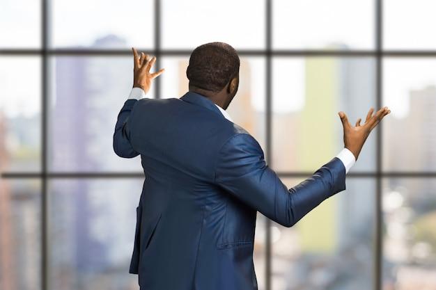 Geschäftsmann von hinten hände heben. rückansicht des verärgerten managers vor dem modernen bürofenster, das arme weit ausstreckt