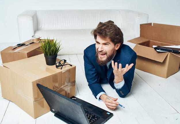 Geschäftsmann vor laptop umzugskarton mit dingen