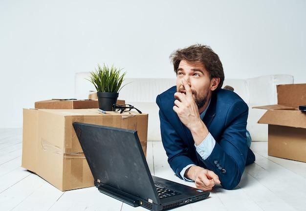 Geschäftsmann vor laptopboxen mit büroarbeitslebensstilsachen