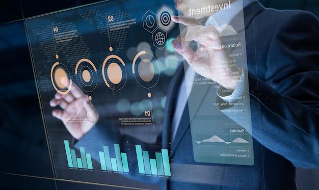 Geschäftsmann vor virtuellem modernen computer-touchscreen, der das investitionsrisikomanagement und die kapitalrenditeanalyse analysiert