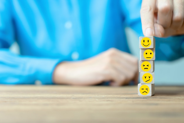Geschäftsmann wählt ein glückliches emoticonikonengesicht. service, kommunikationskonzept