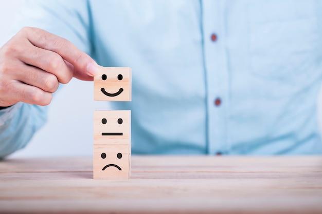 Geschäftsmann wählt ein glückliches symbol des lächeln emoticonikonen-gesichtes auf holzklotz, dienstleistungen und kundenzufriedenheitsumfragekonzept