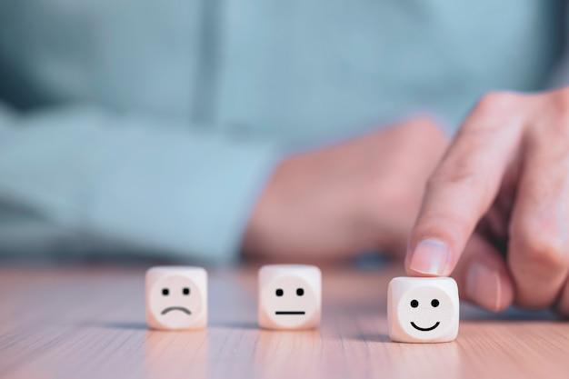 Geschäftsmann wählt ein lächelngesicht, das auf holzklotz glücklich ist