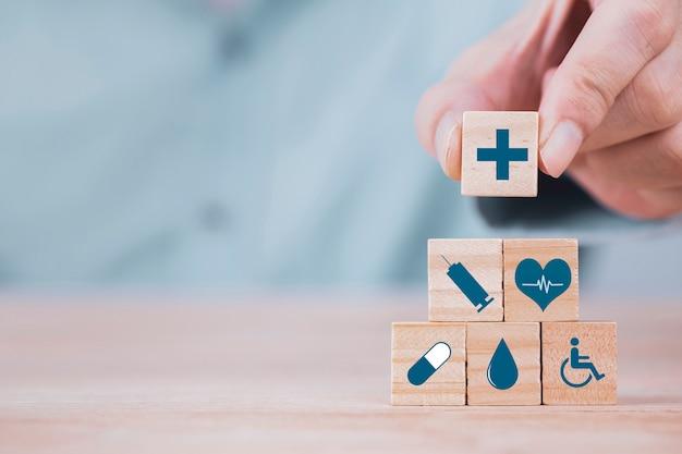 Geschäftsmann wählt ein medizinisches symbol des emoticonikonen-gesundheitswesens auf holzklotz