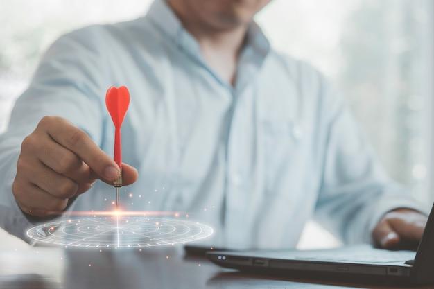 Geschäftsmann wirft roten pfeil auf virtuelle dartscheibe und gibt geschäftsziel auf laptop-computer ein, richtet ziele und zielkonzept ein.